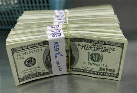 One-hundred-dollar notes are placed on a desk for counting