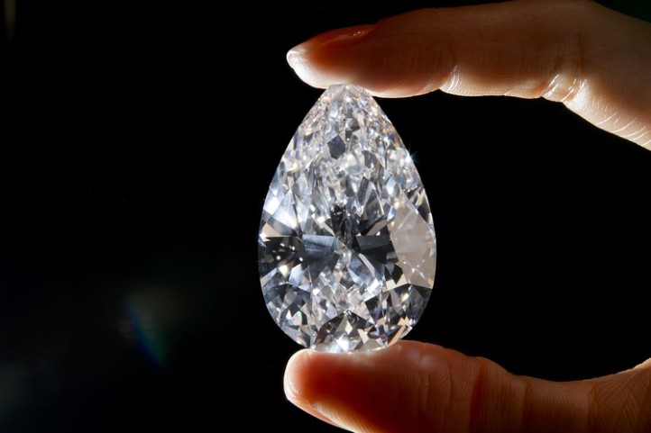 A model holds a diamond weighing 101.73 carats ahead of a sale May 15, 2013