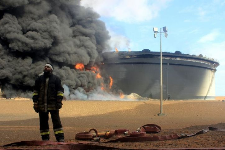 Libyan fireman stands in front of smoke and flames rising from an oil storage tank